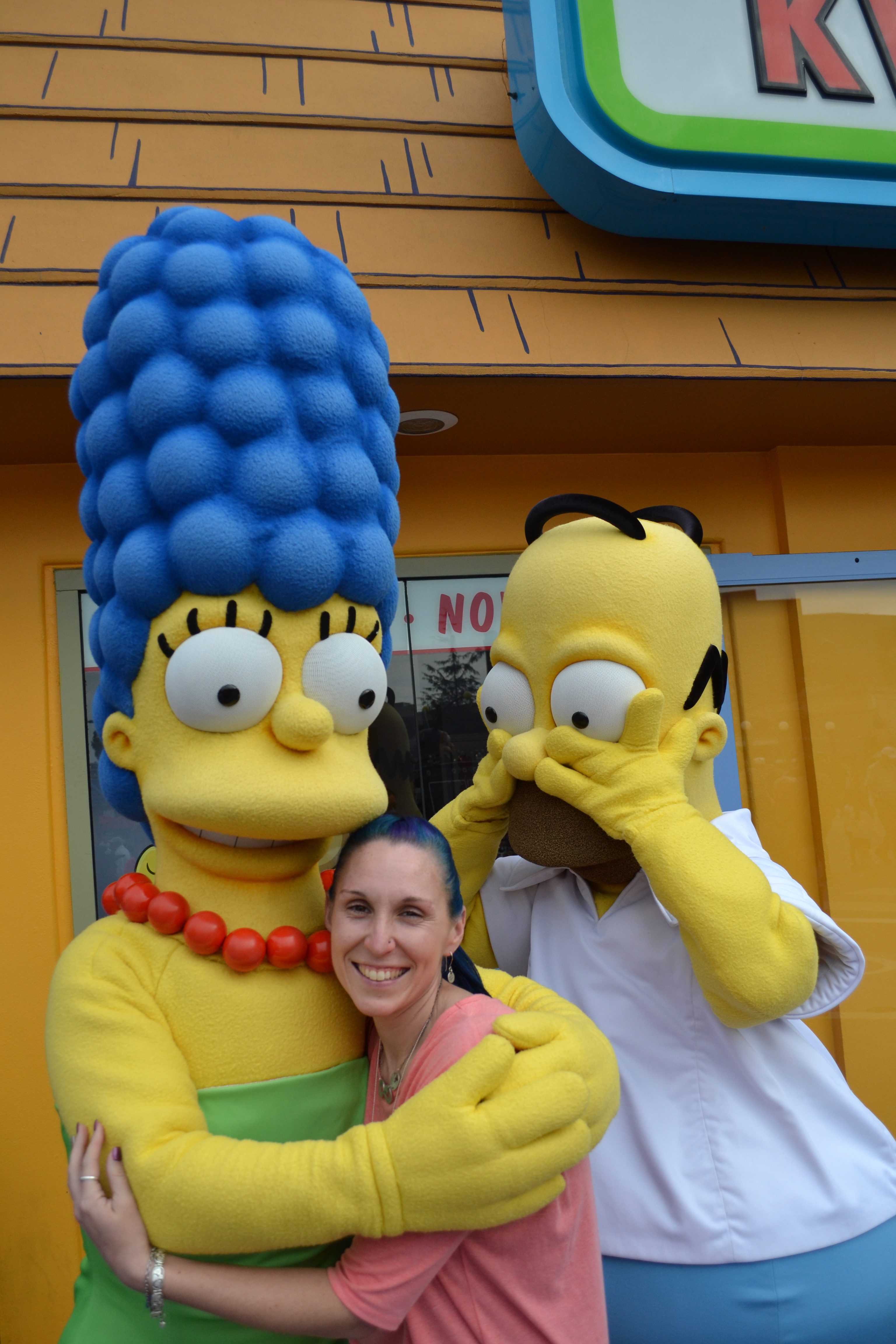 Escort posing with Marge and Homer Simpson at Universal Studios.