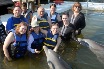 Vacationers and escorts with a friendly dolphin.